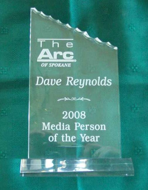 "clear acrilic plaque with stand, with ""The Arc of Spokane,  Dave Reynolds, 2008 Media Person of the Year"" etched in white"
